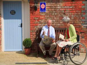 A mature man and woman sitting and talking outside a cottage at Ellwood Cottages, a set of self catering holiday cottages in rural Dorset, England © Britainonview / Pawel Libera