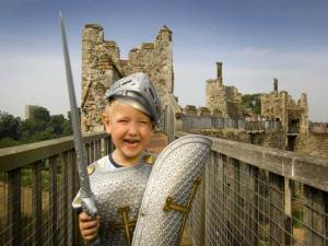Young boy dressed in medieval soldiers outfit at Framlingham Castle in Suffolk © Britainonview / Rod Edwards